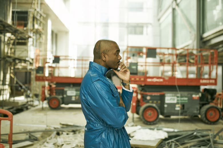 Samuel Ross stands in front of a construction site in London - Building Utopia with A-COLD-WALL*'s Samuel Ross END.