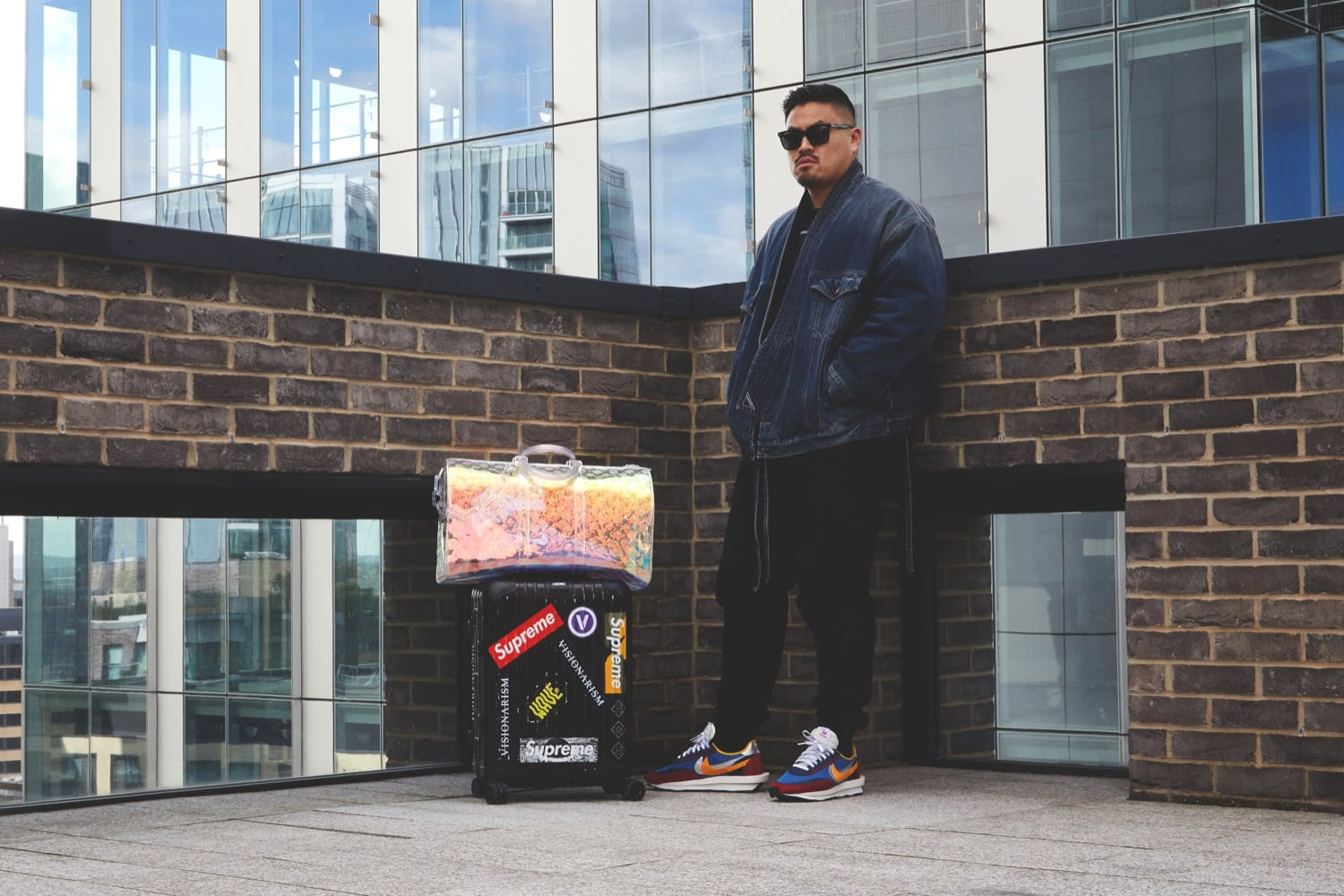 Thierry Tek of Visionarism wearing Sacai x Nike LDWaffle sneakers and Balenciaga jacket with Louis Vuitton holographic hold all and Rimowa flight case for END.