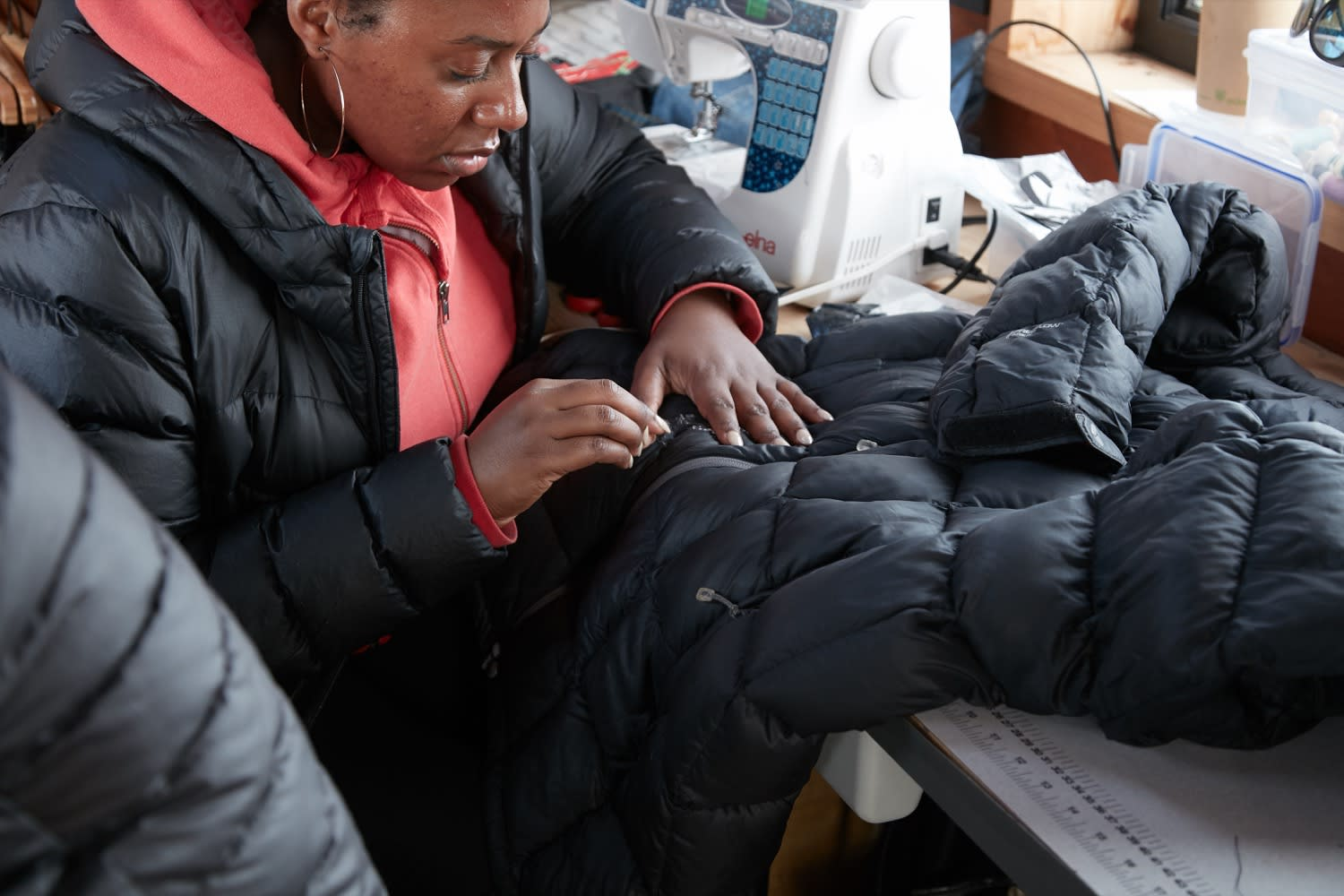 Patagonia Worn Wear seamstress repairing a down coat on Worn Wear Summer Tour 2019