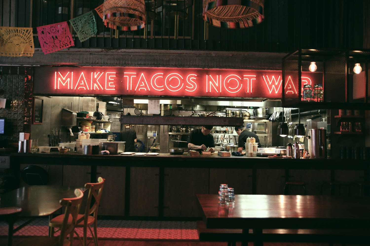 Interior of Tacos & Tequila bar/restaurant with neon 'Make Tacos Not War' sign above kitchen - Axel Arigato City Guide Gothenburg