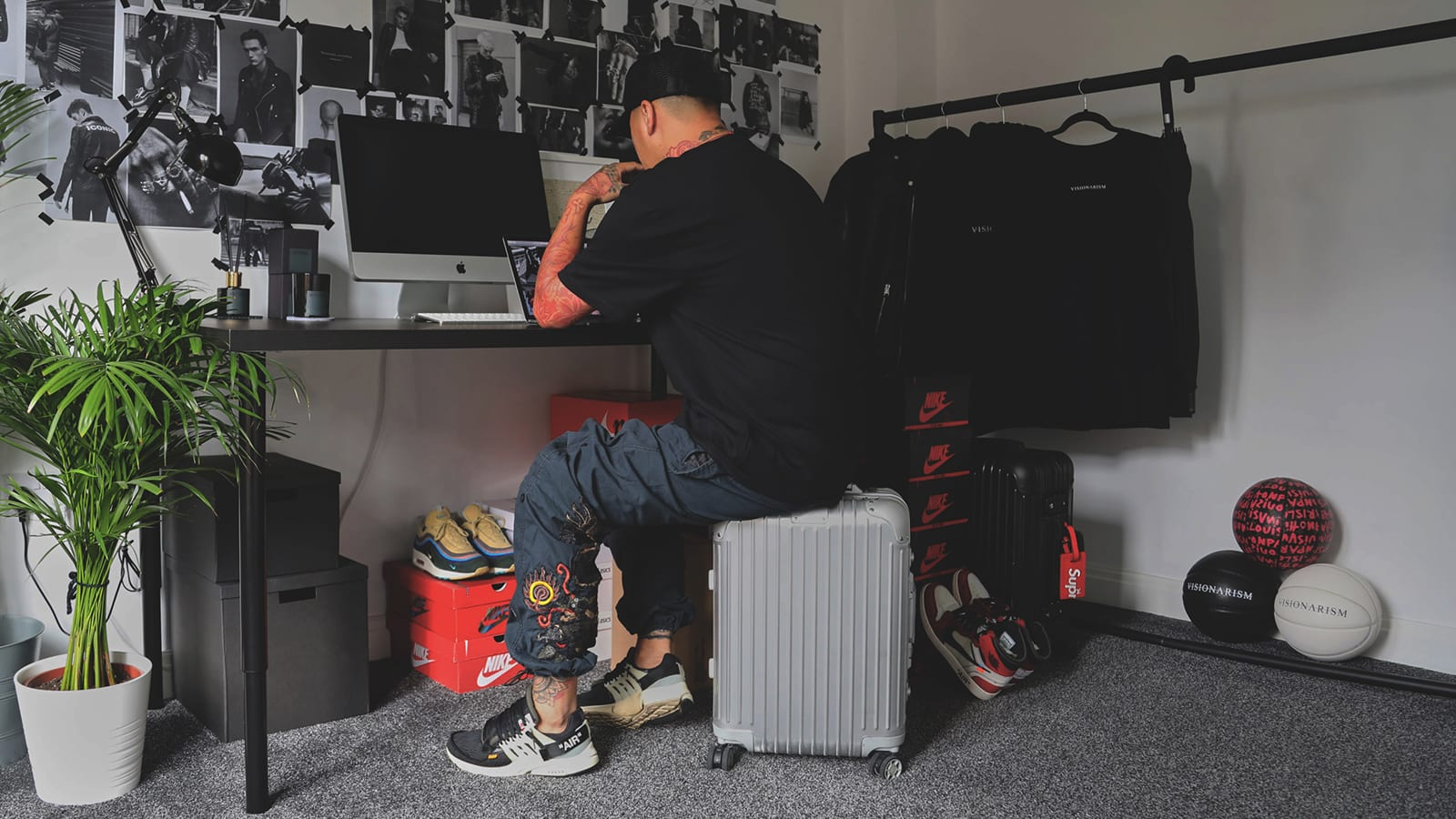 Ste Wing of Visionarism sitting on top of Rimowa travel case in home office with sneakers including Nike x Off-White Presto and AJ1 and Sean Wotherspoon's AM97/1