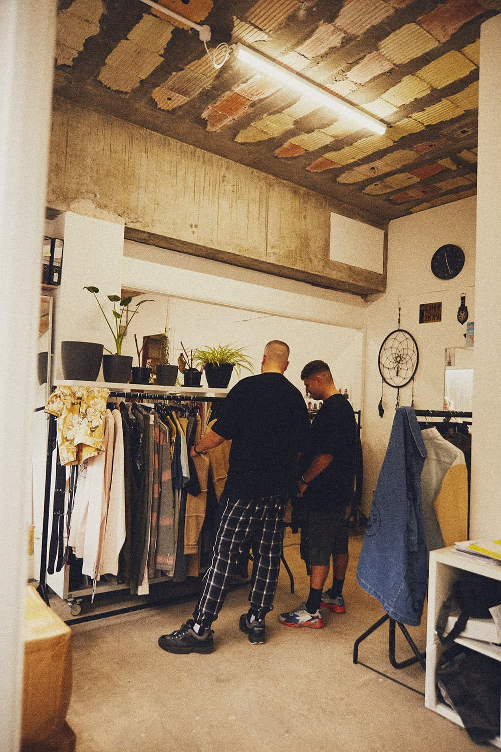 Liam Hodges and Mike Key looking through a rail of new season samples in the Liam Hodges studio